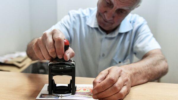Мужчина ставит печать на почтовый конверт - Sputnik Узбекистан