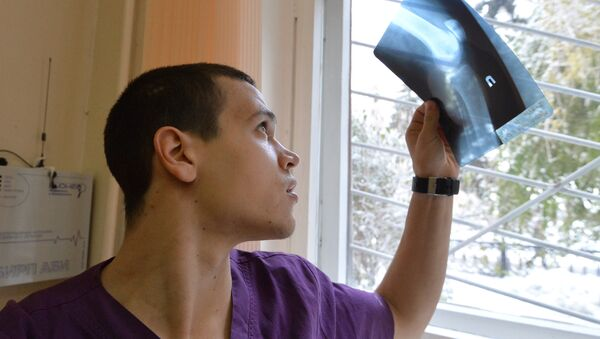 Врач-травматолог смотрит на рентгеновский снимок - Sputnik Узбекистан