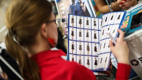 Посетительница изучает каталог производителей школьной формы - Sputnik Ўзбекистон
