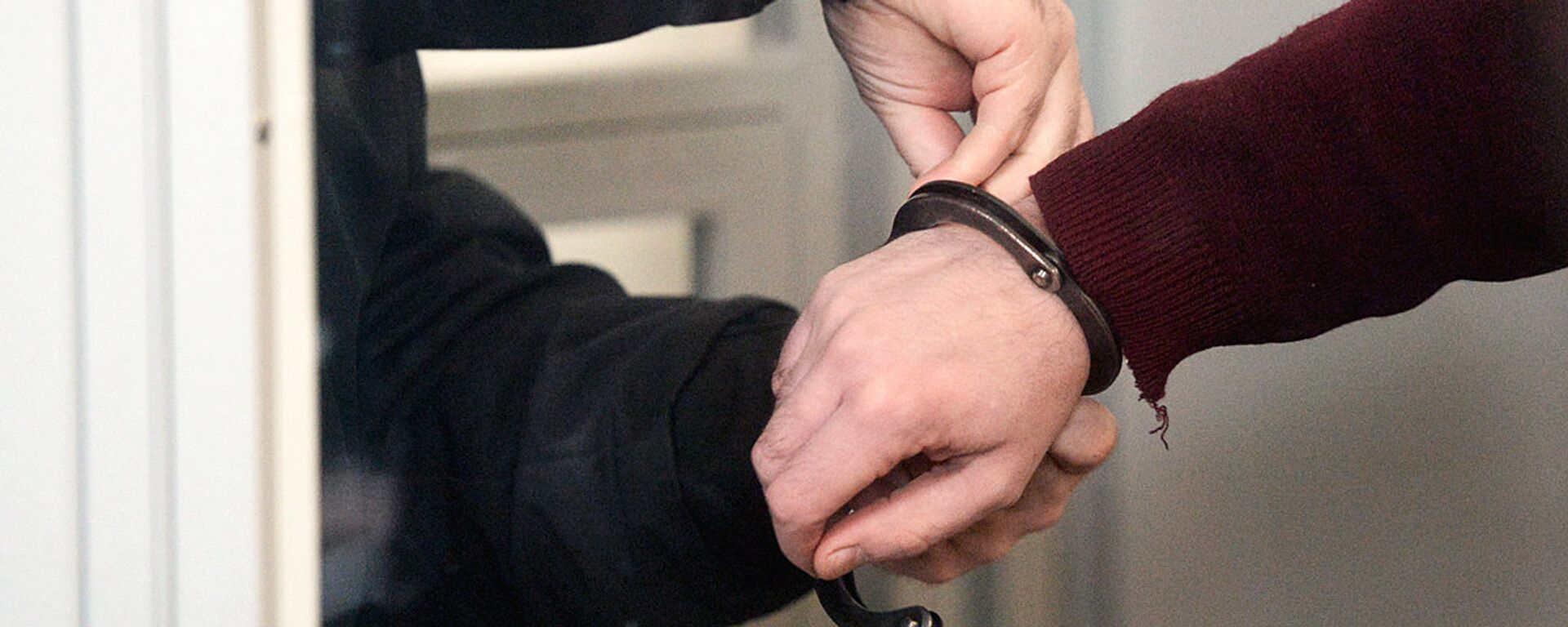 Сотрудник правоохранительных органов снимает наручники - Sputnik Узбекистан, 1920, 02.12.2020