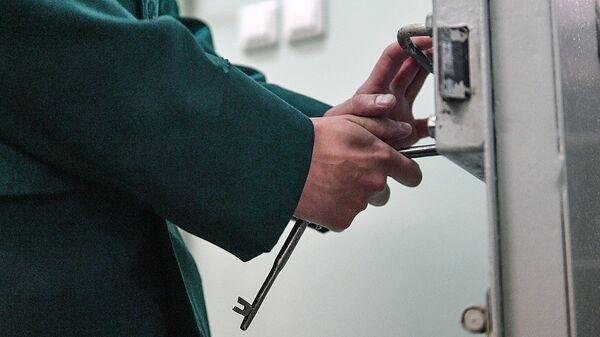 Сотрудник закрывает дверь следственного изолятора - Sputnik Ўзбекистон