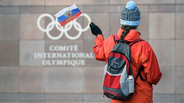 Девушка с российским флагом рядом со штаб-квартирой МОК в Лозанне - Sputnik Узбекистан