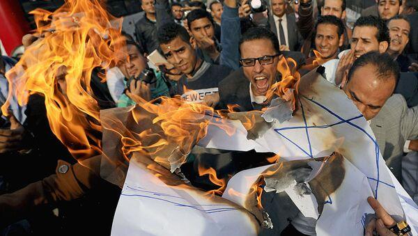 Протестующие кричат лозунги и сжигают израильский флаг во время антиизраильского протеста в Каире, Египет, 10 декабря 2017 года - Sputnik Ўзбекистон