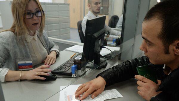 Иностранный гражданин разговаривает с сотрудником центра, получая трудовой патент - Sputnik Ўзбекистон