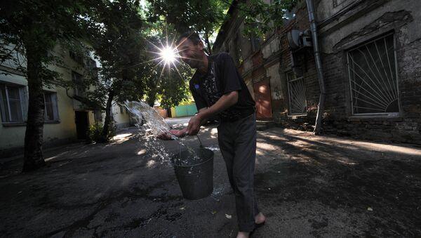 Иностранный рабочий выливает воду из ведра во дворе одного из домов - Sputnik Узбекистан