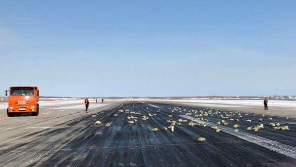 Взлетно-посадочная полоса аэропорта Якутск с рассыпанным грузом из самолёта Ан-12 - Sputnik Ўзбекистон