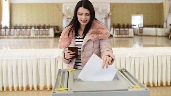 Девушка опускает бюллетень в урну на выборах президента РФ на избирательном участке в Бахчисарае - Sputnik Узбекистан