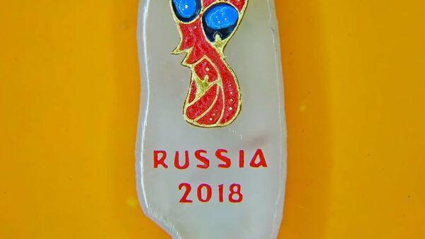 Эмблема чемпионата мира по футболу 2018 года на срезе рисового зернышка, сделанная микроминиатюристом Владимиром Анискиным / - Sputnik Узбекистан