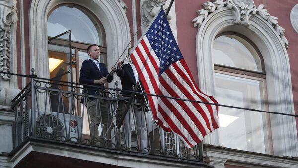 Сотрудники дипмиссии снимают государственный флаг США со здания американского генконсульства на Фурштатской улице в Санкт-Петербурге - Sputnik Узбекистан