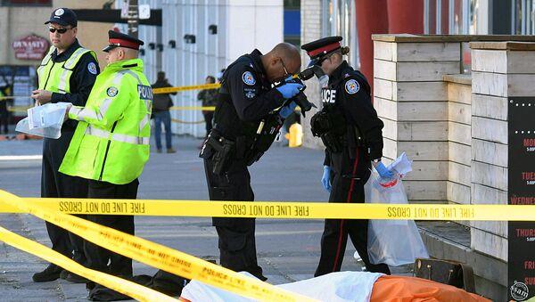 Офицер полиции делает снимок погибшего после того, как фургон протаранил нескольких человек в Торонто - Sputnik Ўзбекистон