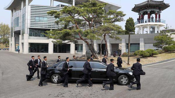 Сотрудники безопасности лидера КНДР Ким Чен Ына сопровождают его автомобиль, который возвращается в Северную Корею на обеденный перерыв во время межкорейского саммита в деревне Пханмунджом в демилитаризованной зоне, разделяющей две Кореи - Sputnik Ўзбекистон