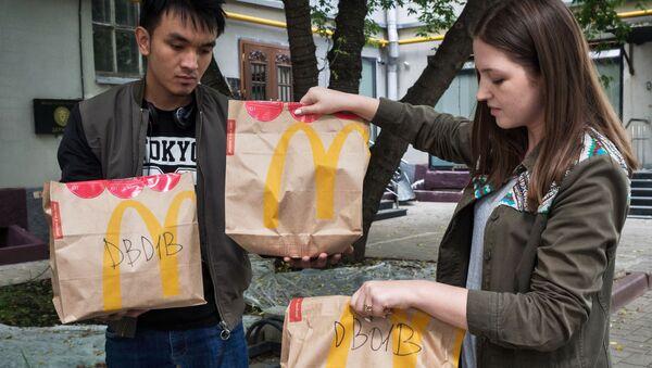 Молодые люди держат пакеты с едой из McDonald's - Sputnik Узбекистан