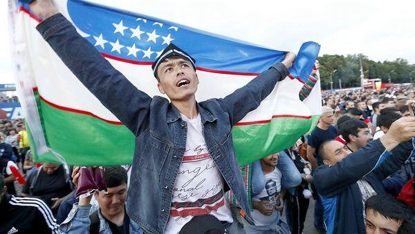 Болельщик с флагом Узбекистана в фан-зоне во время просмотра полуфинального матча ЧМ по футболу Франция - Бельгия  - Sputnik Узбекистан