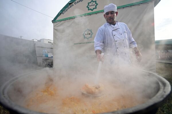 Мужчина готовит плов в комплексе Курбан-байрам в праздник Курбан-байрам в Казани. - Sputnik Узбекистан