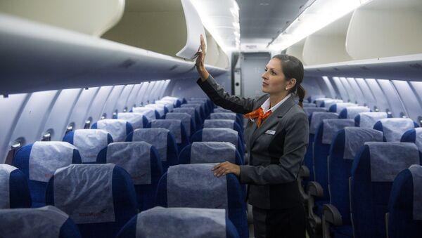 Стюардесса проверяет багажные полки в салоне самолета Sukhoi Superjet 100 - Sputnik Узбекистан