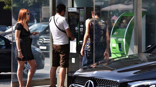 Мужчина оплачивает услуги парковки в Москве - Sputnik Ўзбекистон