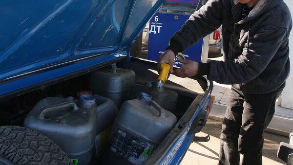 Водитель наливает бензином канистры в багажнике - Sputnik Ўзбекистон