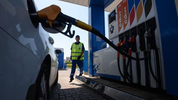 Сотрудник автозаправочной станции заправляет автомобиль клиента - Sputnik Ўзбекистон