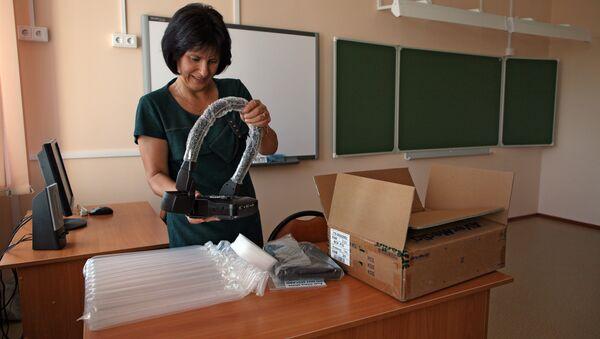 Учитель распаковывает прибор в одном из классов школы - Sputnik Ўзбекистон