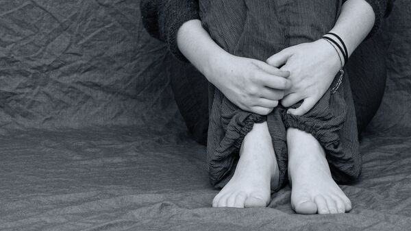 Женщина обнимает ноги. Иллюстративное фото - Sputnik Узбекистан